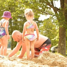 Father and daughters playing in the sand